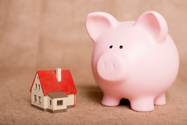 Small model house beside a large pink piggy bank.