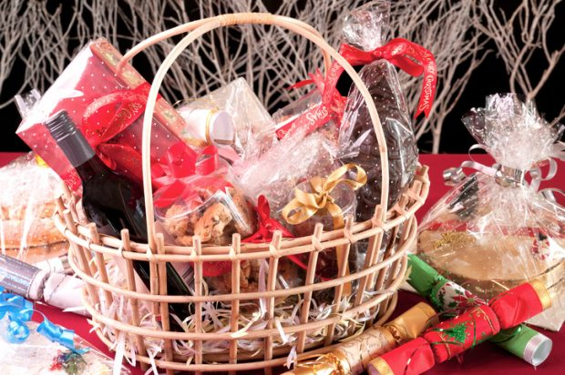 Christmas hamper basket with a chocolate Santa, cookies and a bottle of wine close-up