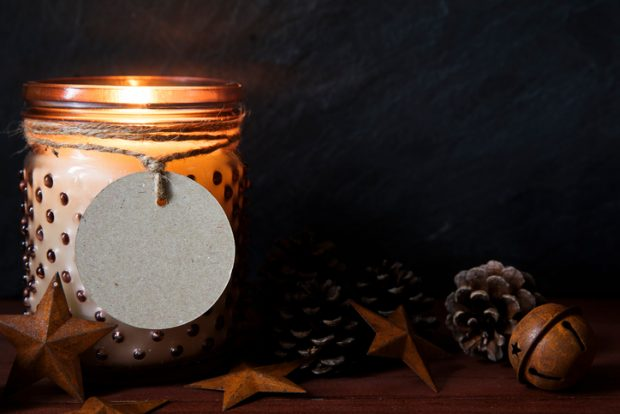 Rustic Christmas scene with jar candle, pine cones, metals stars and round tag with copy space.